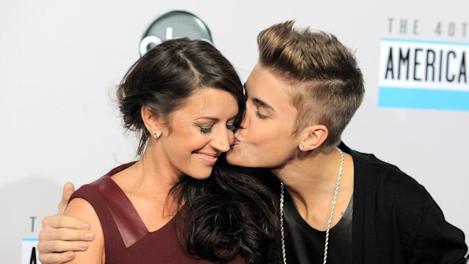"FILE - In this Nov. 18, 2012 file photo, Justin Bieber, right, kisses his mother Pattie Mallette at the 40th Anniversary American Music Awards in Los Angeles. Mallette, has left out some of the rougher details of her early life for a new teen edition of her memoir, ""Nowhere But Up."" Out Tuesday, July 2, 2013, from the inspirational publisher Revell, the book includes advice, statistics and hotline numbers for young people on depression, pregnancy, bullying and unwanted sexual advances. (Photo by Jordan Strauss/Invision/AP, File)"