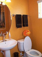 They painted the bathroom orange to match rugs that her husband's aunt made on her loom for them…