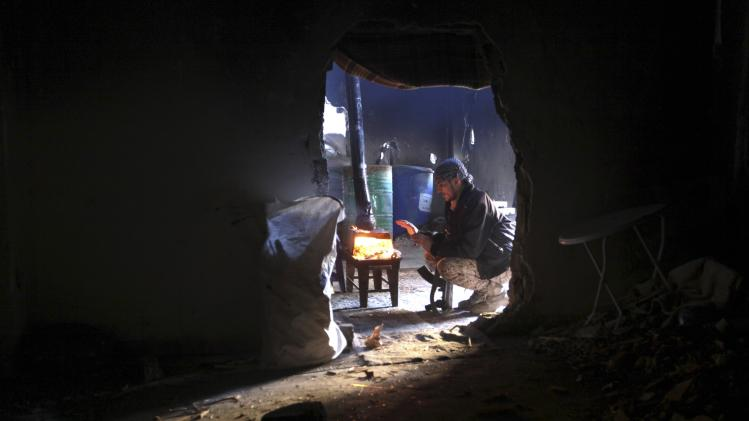 A Free Syrian Army fighter warms himself around a fire as he is seen through a wall opening in Deir al-Zor