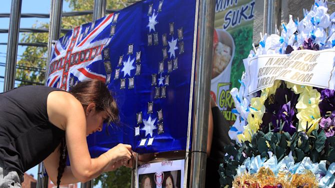A relative of the 2002 Bali bombings attaches the Australian flag to the Bali memorial monument as she pays her respect to victims who were killed in the bombings in Kuta, Bali, Indonesia, Thursday, Oct. 11, 2012. Australian Prime Minister Julia Gillard is scheduled to attend a ceremony commemorating 10 years from the attacks on two nightclubs that killed 202 people, mostly foreign tourists. (AP Photo/Firdia Lisnawati)