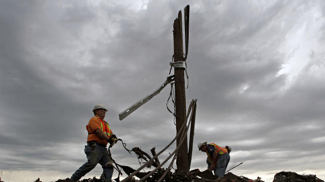 AT&T employees sort through tangled phone lines as they clean up in a tornado-ravaged neighborhood Tuesday, May 21, 2013, in Moore, Okla. A huge tornado roared through the Oklahoma City suburb Monday, flattening entire neighborhoods and destroying an elementary school with a direct blow as children and teachers huddled against winds. (AP Photo/Charlie Riedel)