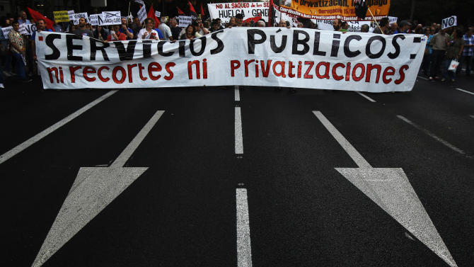 "Protestors hold a banner reading ""public services, no financial cuts, no privatization"" as they shout slogans against healthcare austerity measures announced by the Spanish government in defense of the public healthcare system in Madrid, Spain, Saturday, Oct. 6, 2012. Hundreds of Spaniards concerned with government cuts to healthcare and civil servants hit with another freeze on their wages for next year held a protest in downtown Madrid. (AP Photo/Andres Kudacki)"