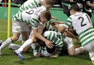 Celtic players celebrate after scoring during an August 2012 match. Two goals in three first-half minutes gave Celtic a 2-0 win at Motherwell on Saturday that sent the Hoops above their opponents and to the top of the Scottish Premier League for the first time this season
