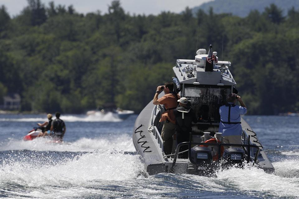 Security personnel follow Republican presidential candidate, former Massachusetts Gov. Mitt Romney and wife Ann Romney as they jet ski on Lake Winnipesaukee in Wolfeboro, N.H., Monday, July 2, 2012. (AP Photo/Charles Dharapak)