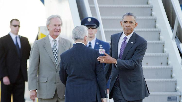 President Barack Obama, right, is greeted on the tarmac by Sen. Jack Reed, D-RI., center, and Gov. Lincoln Chafee, left, upon his arrival at T.F. Green Airport, Friday, Aug. 29, 2014, in Warwick, RI. Obama traveled to Westchester, NY and Rhode Island to attend private Democratic fundraiser's and is returning to Washington later tonight. (AP Photo/Pablo Martinez Monsivais)