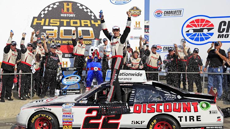 Brad Keselowski poses with his crew in victory lane after winning the NASCAR Nationwide Series History 300 auto race in Concord, N.C., Saturday, May 26, 2012. (AP Photo/Terry Renna)