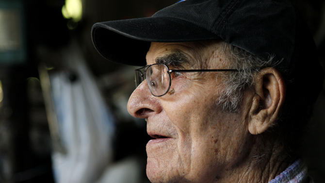 In this Thursday, June 21, 2012 file photo, whirligig artist Vollis Simpson sits outside his shop in Lucama, N.C. Simpson, a self-taught artist famed for his whimsical, wind-powered whirligigs, has died. He was 94. Simpson's wife, Jean, told the Wilson Daily Times that her husband died in his sleep Friday, May 31, 2013. (AP Photo/Gerry Broome)