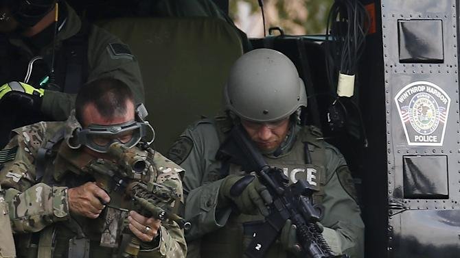 Police officers check their weapons before taking off in a helicopter for a manhunt in Fox Lake