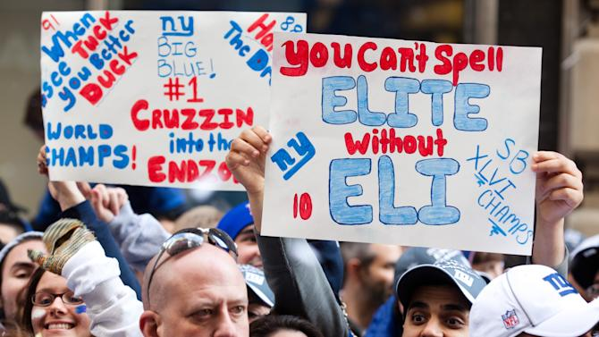 New York Giants fans holds up signs and cheer during the team's NFL football Super Bowl parade in New York, Tuesday, Feb. 7, 2012. The Giants returned from their Super Bowl win to a celebration the likes that only New York can throw: a ticker-tape parade in the Canyon of Heroes on Broadway, where the city has honored stars for almost a century. (AP Photo/John Minchillo)