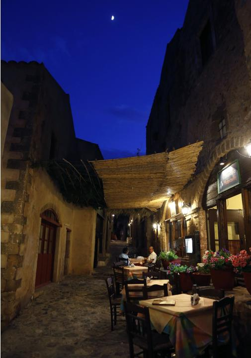 Greek tourists sit in a tavern inside the medieval castle of Monemvasia