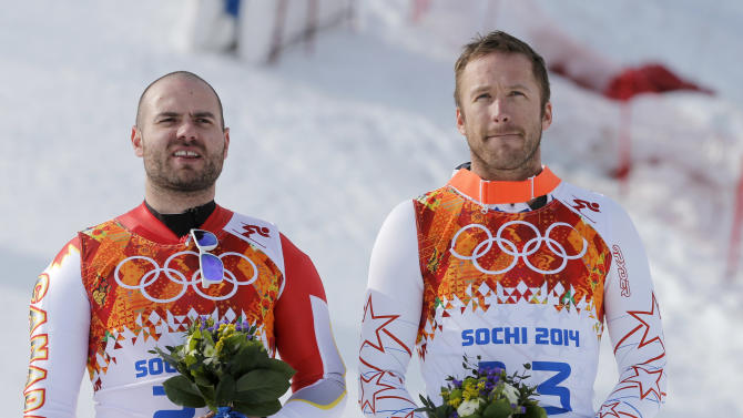 Men's super-G joint bronze medal winners Canada's Jan Hudec, left, and United States' Bode Miller stand on the podium during a flower ceremony at the Sochi 2014 Winter Olympics, Sunday, Feb. 16, 2014, in Krasnaya Polyana, Russia. (AP Photo/Christophe Ena)