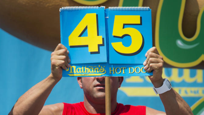 "Sonya ""The Black Widow"" Thomas breaks her world record during the Nathan's Famous Women's Hot Dog Eating World Championship, Wednesday, July 4, 2012, at Coney Island, in the Brooklyn borough of New York. Thomas beat her own record by gobbling down 45 hot dogs and buns in 10 minutes to win the women's competition at the annual Coney Island contest.  (AP Photo/John Minchillo)"