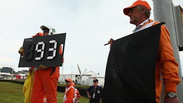 Officials show the black flag to Marc Marquez of Spain as he was disqualified for pitting one lap too late during the Australian MotoGP race at Phillip Island Grand Prix Circuit on October 20, 2013 in Phillip Island, Australia.