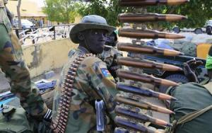 South Sudan army soldier stands next to a machine gun …