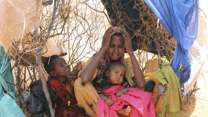 Habiba Osman Ahmed,seated with her two children in a makeshift  shelter in Dollow refugee camp in southern Somalia, Tuesday, Aug. 30, 2011. She was  a former farmer, but since Somalia's 20-year civil war pushed the drought into famine,  everything has changed. Now she doesn't even have a pot to cook in, and must share with another family. She will wait patiently while they finish their food before preparing her own. (AP Photo/Khalil Senosi)