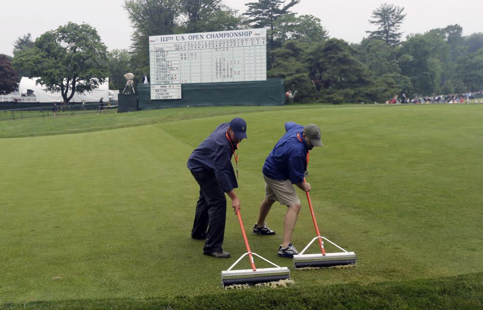 Course workers clear water from the 18th green after a weather delay during the first round of the U.S. Open golf tournament at Merion Golf Club, Thursday, June 13, 2013, in Ardmore, Pa. (AP Photo/Charlie Riedel)