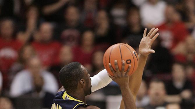 )Ohio State's Lenzelle Smith Jr. (32) tries to block a shot by Michigan's Tim Hardaway Jr. (10) during the first half of an NCAA college basketball game on Sunday, Jan. 13, 2013, in Columbus, Ohio. (AP Photo/Mike Munden)