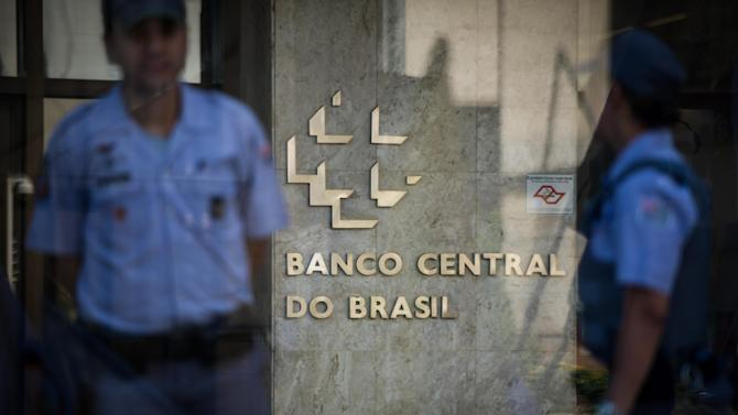Security guards stand by the Central Bank building entrance in Sao Paulo, Brazil, on March 7, 2012