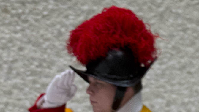 A Swiss Guard salutes as Pope Benedict XVI leaves at the end of his weekly general audience in the Paul IV hall at the Vatican, Wednesday, Jan. 2, 2013. (AP Photo/Andrew Medichini)