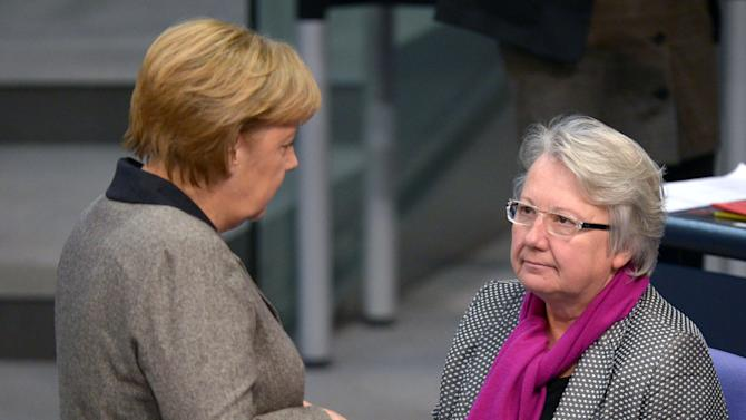 """FILE - in this Dec. 13, 2012 file photo German Chancellor Angela Merkel, left, talks to Education Minister Annette Schavan during a session of the German parliament Bundestag in Berlin, Germany. Schavan says she will not resign after a university stripped her of her doctorate because of plagiarism, and vowed to fight the ruling. Speaking on a trip to South Africa on Wednesday, Feb. 6, 2013, Schavan said she """"will not accept"""" the school's decision and would take legal action against it. (AP Photo/dpa, Rainer Jensen, File)"""