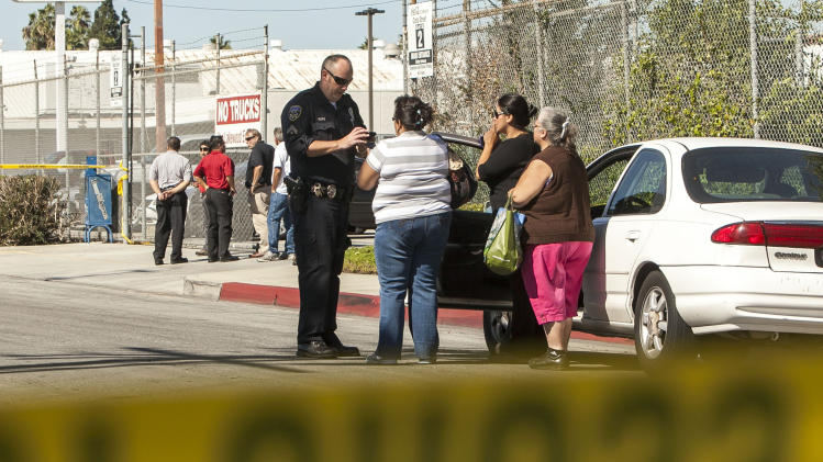 Police investigators talk to people across the street from a family-owned business, United States Fire Protection Services, in Downey, Calif., Wednesday, Oct. 24, 2012.  Five people were shot and at least two died in shootings at the business and a residence in a Los Angeles suburb Wednesday, according to Downey police Lt. Dean Milligan. The shootings occurred shortly after 11 a.m. at a business and at a nearby home, where family members of the business owner live. A woman was found dead at the home, he said. (AP Photo/Damian Dovarganes)