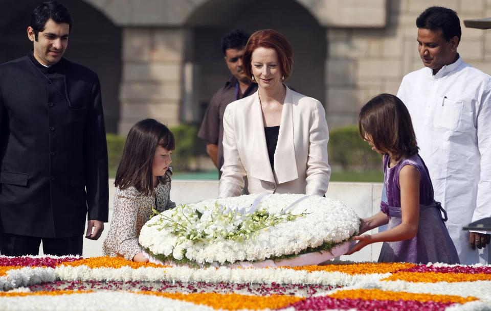 Australian Prime Minister Julia Gillard, center, accompanied by unidentified children pays floral respects at the memorial of Mahatma Gandhi in New Delhi, India , Wednesday, Oct. 17, 2012. (AP Photo/Mustafa Quraishi)