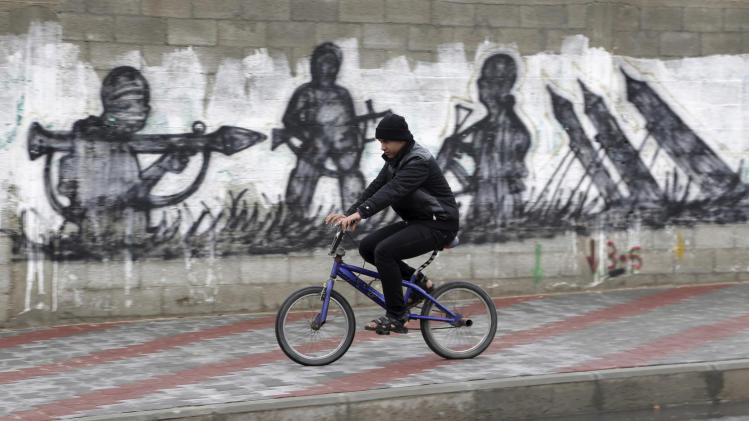 "A Palestinian rides his bicycle near graffiti of rockets and militants in Gaza City, in the northern Gaza Strip, Thursday, March 13, 2014. Gaza militants resumed their rocket fire toward Israel on Thursday, striking the outskirts of two major cities a day after launching the largest barrage since an eight-day Israeli offensive in late 2012. Gaza militant groups said they resumed their rocket fire in response to what they say are Israeli ""provocations"" and violations of a cease-fire, including an airstrike that killed three Islamic Jihad militants earlier this week. (AP Photo/Adel Hana)"