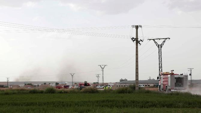 Fire trucks and emergency vehicles gather as smoke rises from the Pirotecnia Zaragozana fireworks factory following an explosion, in Zaragoza, northeastern Spain, on August 31, 2015