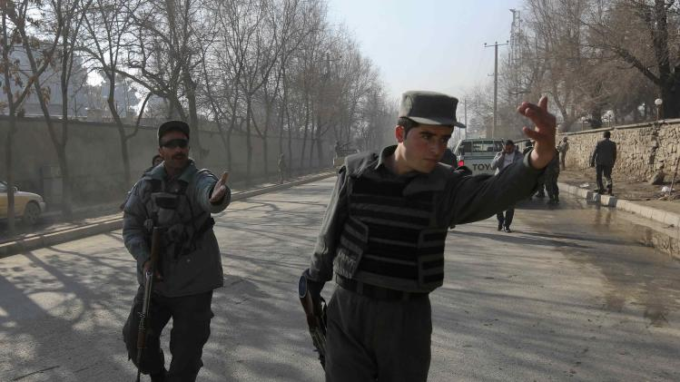 Afghan policemen keep watch at the site of an explosion in Kabul