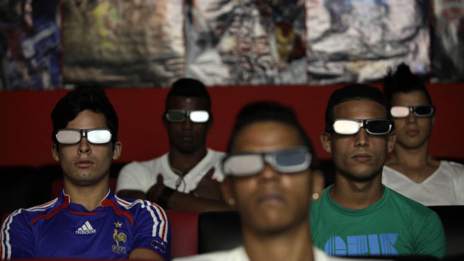 People watch a 3D movie at a private movie theater in Havana, Cuba, Monday, Oct. 28, 2013. Cuban entrepreneurs have quietly opened dozens of backroom video salons over the last year, seizing on ambiguities in licensing laws to transform cafes and children's entertainment parlors into a new breed of private business unforeseen by recent official openings in the communist economy. (AP Photo/Franklin Reyes)