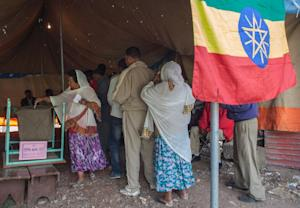 An Ethiopian woman casts her ballot as other queue…