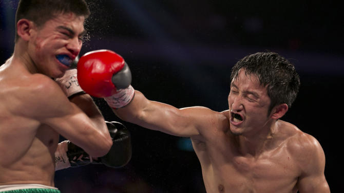 In this July 27, 2013 photo, China's Zou Shiming, right, fights against Mexico's Jesus Ortega during their Flyweight bout at the Cotai Arena in Venetian Macao in Macau. The Chinese fighter's victory at a Macau showdown brings the world's top casino market a step closer to challenging Las Vegas for dominance of another Sin City staple: big-time boxing matches. Macau, which long ago eclipsed Vegas as the world's top gambling city, is now looking to add to its allure by holding the kind of boxing bouts that Las Vegas is known for. (AP Photo/Dennis Ho)