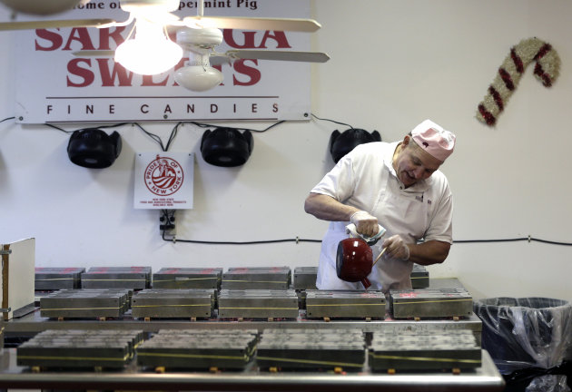In this Dec. 6, 2012, photo, Mike Fitzgerald pours hot peppermint mixture into a mold while making peppermint pigs at his Saratoga Sweets store in Halfmoon, N.Y. A holiday tradition in upstate New Yor