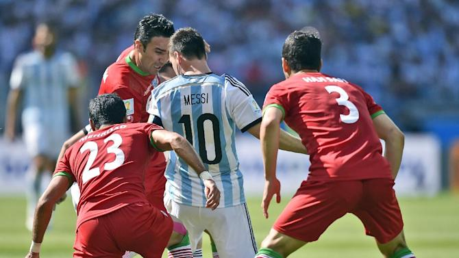 Argentina's Lionel Messi is boxed in by Iran's Mehrdad Pooladi (23) and Ehsan Haji Safi (3) during the group F World Cup soccer match between Argentina and Iran at the Mineirao Stadium in Belo Horizonte, Brazil, Saturday, June 21, 2014