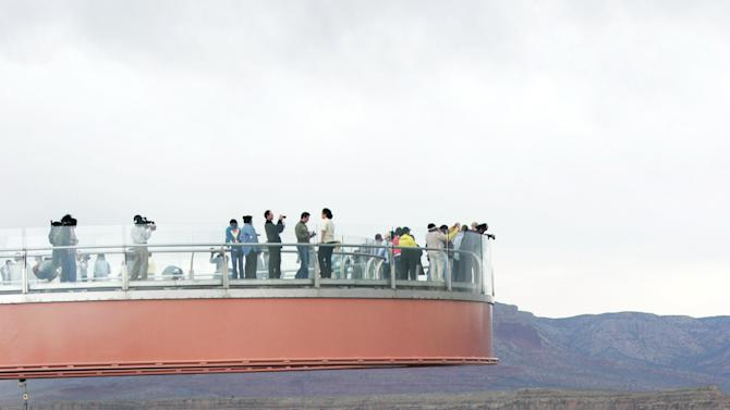 FILE - This March 20, 2007 file photo shows people walking on the Skywalk during the First Walk event at the Grand Canyon on the Hualapai Indian Reservation at Grand Canyon West, Ariz. David Jin the Chinese tour operator and Las Vegas businessman and who built this Grand Canyon Skywalk attraction in northwestern Arizona has died in Los Angeles. A Grand Canyon Skywalk Development spokesman said that Jin died Thursday June 13, 2013 at UCLA Medical Center after a four-year battle with cancer. He was 51.(AP Photo/Ross D. Franklin, file)