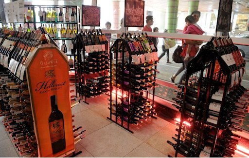 Pedestrians walk past a store selling alcoholic beverages at a mall in Manila on January 1, 2013