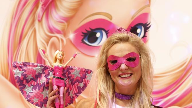 Woman, dressed as 'Barbie' doll, poses with new 'Barbie' doll during press preview of International Toy Fair in Nuremberg