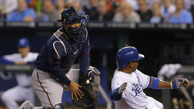 Kansas City Royals' Alcides Escobar (2) slides safely past Minnesota Twins catcher Kurt Suzuki during the third inning of a baseball game at Kauffman Stadium in Kansas City, Mo., Friday, April 18, 2014. Escobar scored on a single by teammate Omar Infante. (AP Photo/Orlin Wagner)