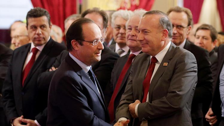 """French President Francois Hollande, left, shakes hand with French employer's body MEDEF union leader Pierre Gattaz at the end of a New Year ceremony for employment sector representatives at the Elysee Palace in Paris, Tuesday, Jan. 21, 2014. French President Francois Hollande warned companies that they have to hire large numbers of French workers, especially the young and old, if they want to benefit from a promised 30-billion-euro cut in payroll taxes. Hollande is counting on his so-called """"responsibility pact"""" to revive growth in the stagnant economy and reduce nearly 11 percent unemployment. (AP Photo/Philippe Wojazer, Pool)"""