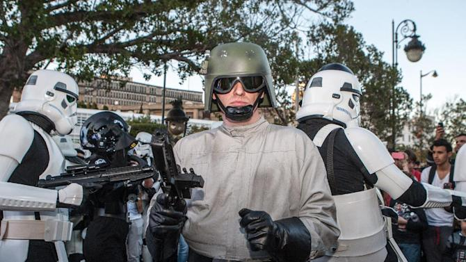 """Star Wars fans wearing stormtrooper costumes parade along Tunis' stately, tree-lined Bourguiba Avenue, in Tunisia, Wednesday, April 30, 2014. The empire was not striking back against the poster child for Arab democracy — just an innovative campaign to encourage tourists to return to this sunny desert-and-beach nation in North Africa. """"We came here to Tunis to help save the Star Wars sites in Matmata and Tozeur and convince people to return to Tunisia,"""" said Ingo Kaiser, head of a Star Wars fan club in Europe, referring to the movie sets that are slowly being covered up by sand in the Tunisian desert. (AP Photo/Aimen Zine)"""