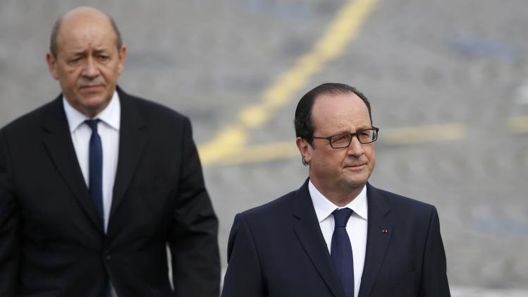 France's President Francois Hollande and French Defence Minister Jean-Yves Le Drian arrive to attend the traditional Bastille Day parade on the Place de la Concorde in Paris
