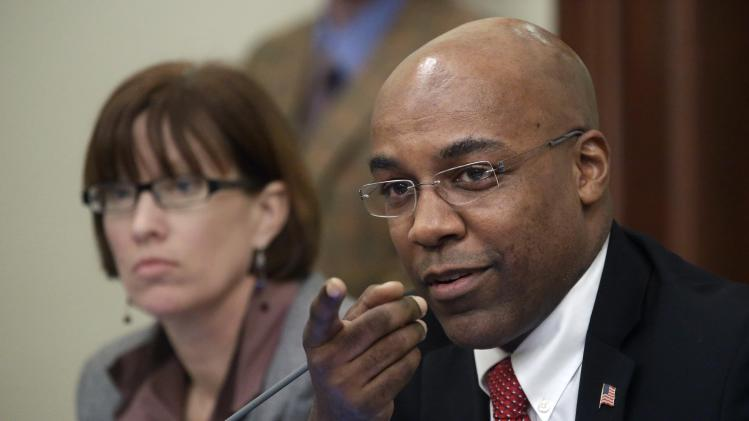 Illinois Sen. Kwame Raoul, D-Chicago, ask questions during a committee hearing at the Illinois State Capitol Wednesday, Jan. 2, 2013 in Springfield, Ill. Illinois Senate Democrats seeking assault-weapon restrictions planned to split the issue, seeking committee approval of a ban on high-capacity ammunition clips and a separate restriction on semi-automatic guns. (AP Photo/Seth Perlman)