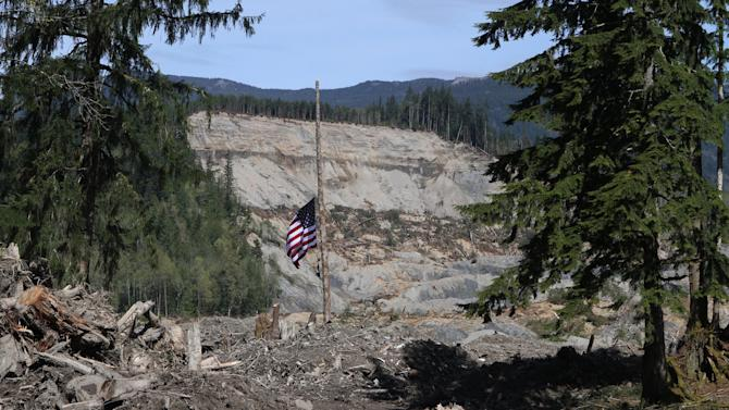 A flag honoring victims of the Oso mudslide hangs at half staff , Tuesday, April 29, 2014 in Oso, Wash. The local access road has opened through the Oso mudslide, connecting the stretch of Highway 530 blocked by the March 22 landslide. (AP Photo/The Seattle Times, Ellen M. Banner, Pool)