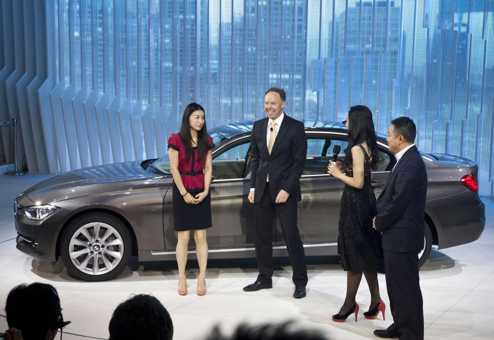 BMW marketing chief Ian Robertson, center, and Olympic gold medalist diver Guo Jingjing, left, share a light moment after the company unveiled the new BMW 3-series long wheel base 335L model at the Beijing International Automotive Exhibition in Beijing, China Monday, April 23, 2012. (AP Photo/Andy Wong)