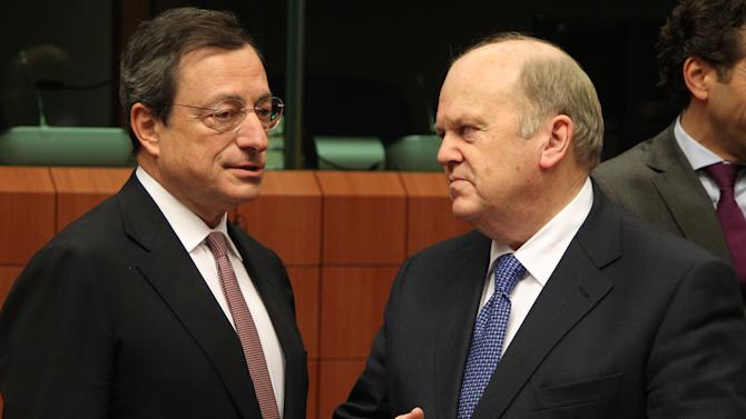 "President of the European Central Bank Mario Draghi, left, talks with Irish Finance Minister Michael Noonan, during the Eurogroup finance ministers meeting in Brussels, Monday, Nov, 12, 2012. Greece's international lenders have prepared a ""positive"" report on the country's reform efforts, a crucial step in its efforts to secure the next installment of its bailout loan, the head the of group of finance ministers from the 17 euro countries said Monday. (AP Photo/Yves Logghe)"