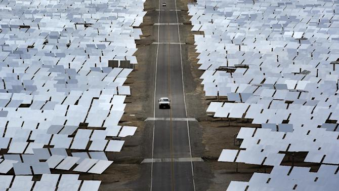 In this Aug. 13, 2014 photo, A truck drives through an array of mirrors at the Ivanpah Solar Electric Generating System near Primm, Nev. The site uses over 300,000 mirrors to focus sunlight on boilers' tubes atop 450 foot towers heating water into steam which in turn drives turbines to create electricity. New estimates for the plant near the California-Nevada border say thousands of birds are dying yearly, roasted by the concentrated sun rays from the mirrors. (AP Photo/John Locher)