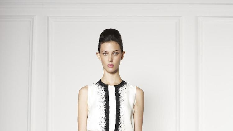 This undated image released by Carolina Herrera, a model wears a white tiered cocktail dress trimmed with black lace from the Carolina Herrera 2013 resort collection. (AP Photo/Carolina Herrera)