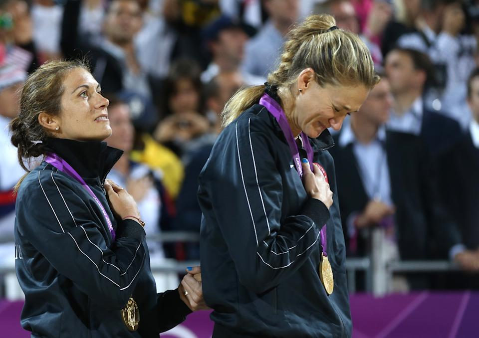 United States' Kerri Walsh Jennings, right, and Misty May-Treanor, left, listen to anthem during a podium ceremony after winning the women's gold medal beach volleyball match at the 2012 Summer Olympics, Wednesday, Aug. 8, 2012, in London. (AP Photo/Petr David Josek)