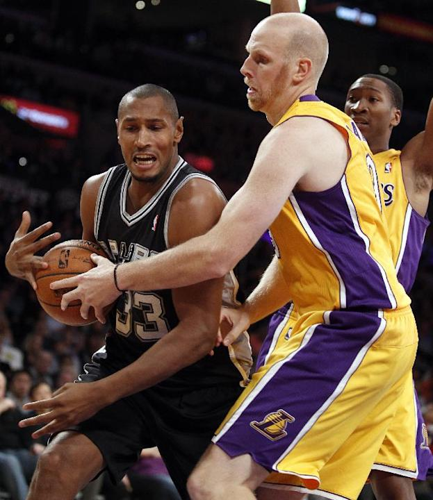 San Antonio Spurs forward Boris Diaw, left, of France, secures the ball as Los Angeles Lakers center Chris Kaman, front right, attempts to steal with Lakers guard Wesley Johnson, back right, looking o