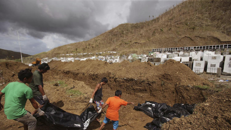 Workers start to arrange body bags at a mass burial site at the Basper public cemetery in Tacloban, Leyte province, central Philippines on Thursday, Nov. 14, 2013. Workers in the typhoon-shattered city buried 100 of its thousands of dead in a hillside mass burial Thursday as desperately needed aid began to reach some of the half-million people displaced by the disaster. (AP Photo/Aaron Favila)
